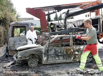 Police examine a burnt-out car in Hildesheim