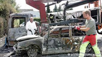 Firemen stand next to a burnt out car