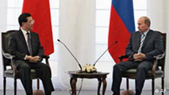 Russian President Vladimir Putin, right, and Chinese President Hu Jintao speak during a meeting after joint military exercises at Chebarkul testing range in Russia, on Friday, Aug. 17, 2007. President Vladimir Putin said Friday that he had ordered the military to resume regular long-range flights of strategic bombers, news agencies reported. Russian and Chinese forces on Friday held their first joint maneuvers on Russia's territory. The war games in Russia's southern Ural Mountains involved some 6,000 troops from Russia and China and also a handful of soldiers from four ex-Soviet Central Asian nations that are part of the Shanghai Cooperation Organization, a regional group dominated by Moscow and Beijing. (AP Photo/RIA-Novosti, Dmitry Astakhov, Presidential Press Service)
