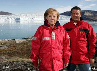 German Chancellor Angela Merkel and German environment minister Sigmar Gabriel pose in front of the Eqi glacier near Ilulissat, Greenland