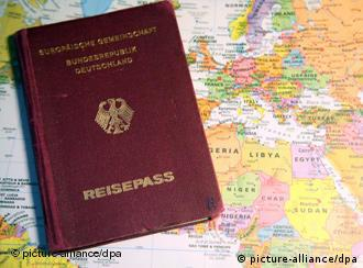 A German passport lies on a map of the world