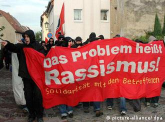 Demonstrators carry a banner reading racism's the problem to show solidarity with Indian victims of a racist attack in the town of Muegeln in eastern Germany
