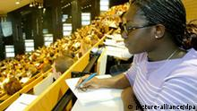 A female student from Africa takes notes in a lecture hall