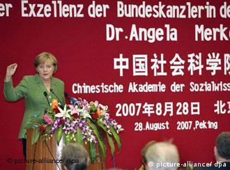 Merkel am Rednerpult, im Hintergrund eine rote Wand mit weißer Beschriftung (Quelle: dpa)