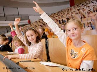 Children stick their hands in the air to ask a question at the Karlsruhe Children's University