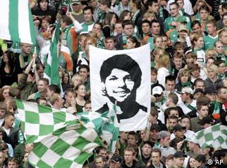 Supporters of Werder Bremen show a picture of Bremen player Diego