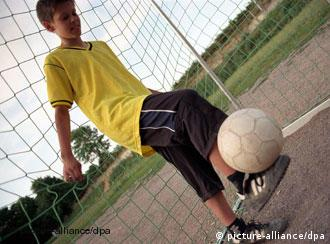 A teenage boy plays with a soccer ball