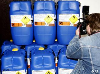A man photographs canisters of hydrogen peroxide