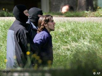 An arrested terror suspect is lead away from a court by two masked police officers