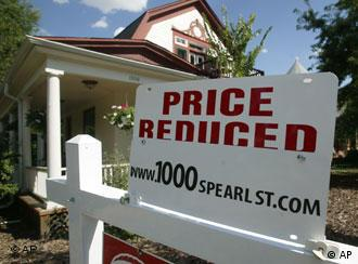 A sign to inform prospective buyers that the price has been reduced sits on top of the sale sign outside a single-family home in south Denver