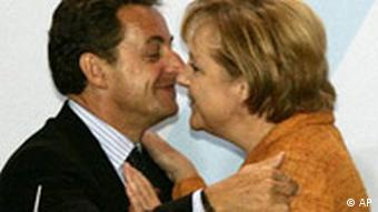 Sarkozy and Merkel greet each other with a kiss on the cheek