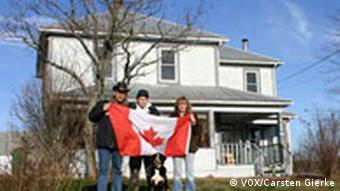 Family stands in front of house with Canadian Flag