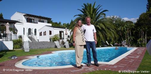 Ein Paar steht vor ihrem Pool vor weißer Villa in Südafrika.