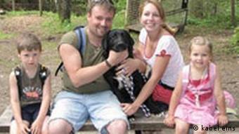 Eine junge Familie mit Hund im Portraitfoto.