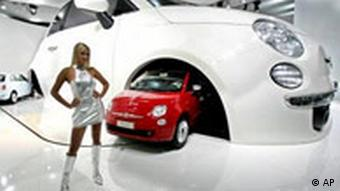 A hostess is seen in front of a large model of an old Fiat 500 car where a new Fiat models drive through at the International Auto Show in Frankfurt
