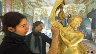 Restorers work on a golden statue in Potsdam's New Palace