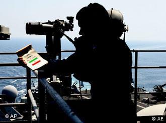 یک سرباز نیروی دریای آمریکایی بر روی ناوی در خلیج فارس − او دفترچهی راهنمایی در مورد کشتیهای ایران در دست دارد (عکس از آرشیو، ۲۰۰۷)