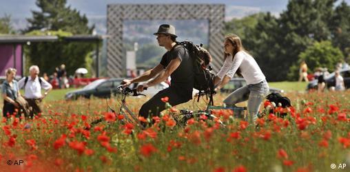 Zwei Radfahrer radeln durch ein Mohnfeld. Quelle: AP