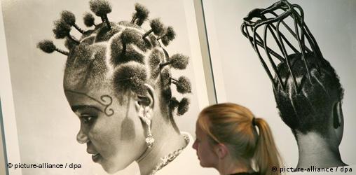 Eine blonde Frau betrachtet großformatige schwarz-weiß Fotos von Frauen mit afrikanischen Frisuren. Quelle: dpa