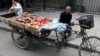 A street vendor waits for customer, showing tomatoes and potatoes on his tricycle's back, on a backstreet in Beijing, Monday, Sept. 24, 2007. China said Monday it had boosted inspections of agriculture products nationwide in a bid to cut the use of banned pesticides and the overuse of animal feed additives and fertilizers. (AP Photo/Shuji Kajiyama)