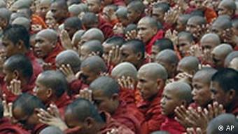 Myanmar Buddhist monks pray before taking up the street in a march protesting against the military government