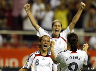 Germany's Birgit Prinz exults with Sandra Smisek, left, and Kerstin Garefrekes