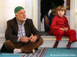 A man and small child sit in a mosque