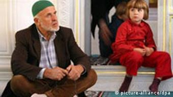 A young boy sits looking at an older Muslim man