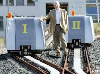 Professor Joachim Lueckel stands with prototypes of the RailCab