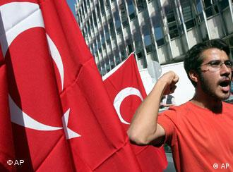 A demonstrator, with Turkish flags next to him, shouts anti-American slogans during a protest