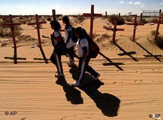 Niñas pasan por unas cruces que recuerdan a las víctimas de la violencia en Ciudad Juárez.