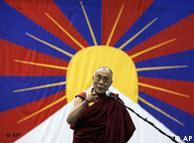 Dalai Lama standing in front of a Tibetan flag