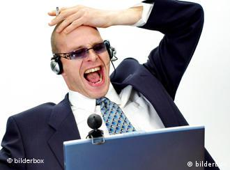 A man with headphones yelling at a laptop computer