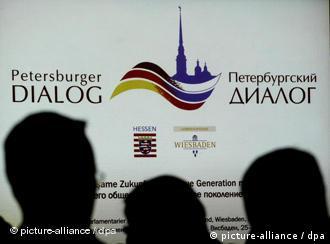 Люди на фоне эмблемы Петербургского диалога