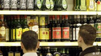 Two men stand before shelves stocked with alcohol