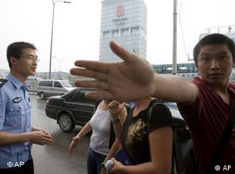 a policeman questions journalists in Beijing
