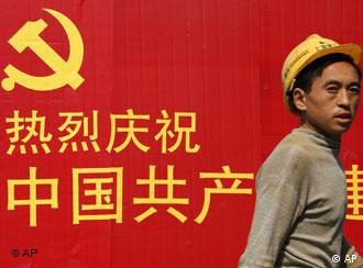 A construction worker walks past an official propaganda of Chinese Communist Party Friday Oct. 19, 2007 in Shanghai, China. Chinese Communist Party leaders have kept out of the public eye this week in a possible sign of deepening closed-door deliberations over appointments that will determine China's leadership and influence policy-making for the next five years. (AP Photo/Eugene Hoshiko)