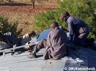 Insatalando placas solares sobre el tejado de una escuela en Zambia.
