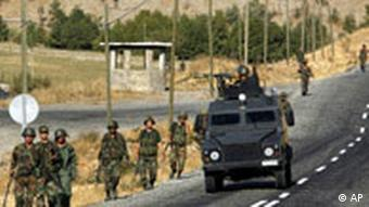 Turkish soldiers, carrying land mine detectors, patrol beside a road in the province of Sirnak