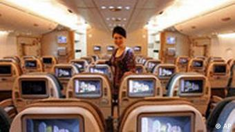 A Singapore Airlines air stewardess poses among the economy seats in the Airbus A380 jetliner