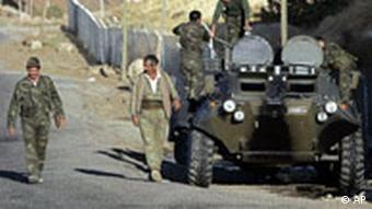 Turkish pro-government village guards, left, patrol past soldiers maintaining their armored vehicle, in the area near Turkey-Iraq border, in Sirnak, Turkey, in October, 2007. (AP Photo/Darko Bandic)