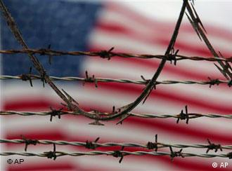A blurred view of a US flag behind the barbed and razor-wire at the Guantanamo Bay camp in Cuba