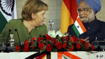Angela Merkel talking to PM Singh at a table covered in roses, with the Indian and German flags in the background