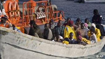 A Spanish rescue ship tows a boat with 60 would-be immigrants aboard after being intercepted as it crossed over from western Africa, in Puerto de los Cristianos, on the Spanish Canary Island of Tenerife, Monday, Nov. 5, 2007. Thousands of African immigrants arrive by boat every year trying to find a better way of life in Europe. The dangerous trip often takes more than a week and many die in the attempt. (AP Photo/Arturo Rodriguez)