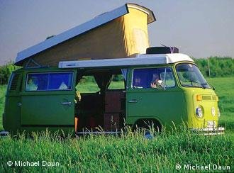 A green VW Bulli bus stands on a meadow