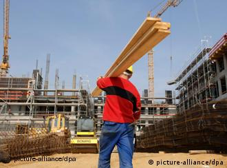 A construction worker carries logs at a building site