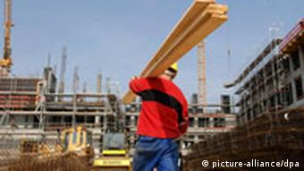 Polish worker carries wood on a building site