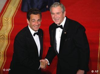 President George W. Bush and President Nicolas Sarkozy, both in tuxedos, shake hands