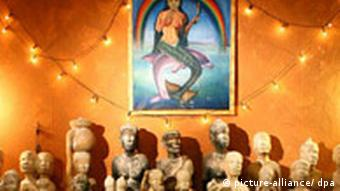 Statues used in voodoo worship arranged beneath a painting of goddess Mami Wata