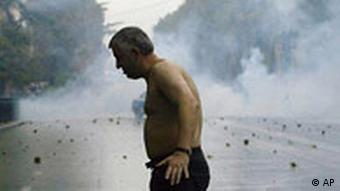 A shirtless man hit by tear gas stands amidst a confrontation between security forces and anti-government protesters outside the parliament in Tbilisi, Georgia